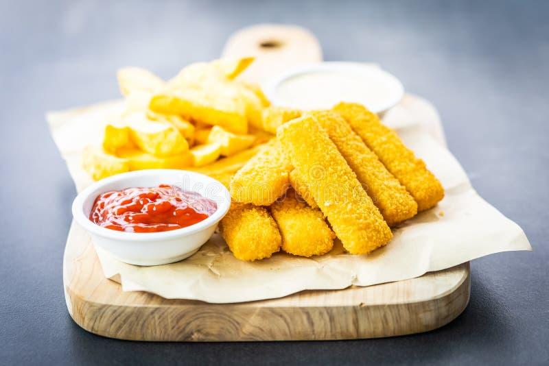 Bâton de poisson et pommes frites ou pommes chips avec le ketchup de tomate et la sauce à mayonnaise image libre de droits