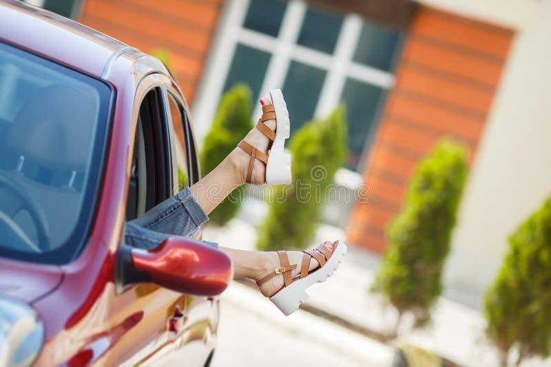 Bâton femelle de jambes hors d'une fenêtre de voiture image stock
