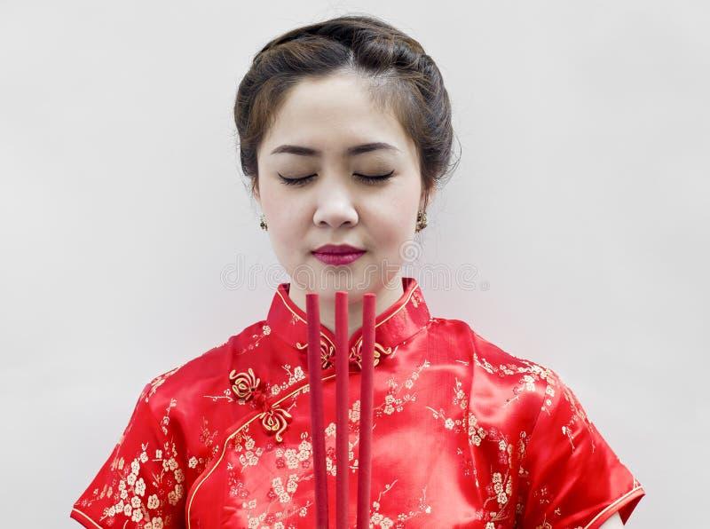 Bâtons d'encens chinois de fixation de jeune femme images stock