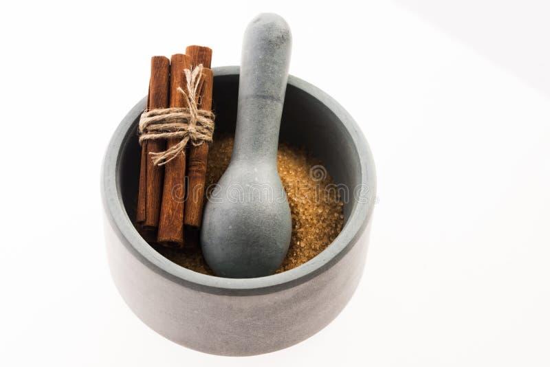 Bâtons de cannelle avec du sucre roux pur de canne en mortier image stock