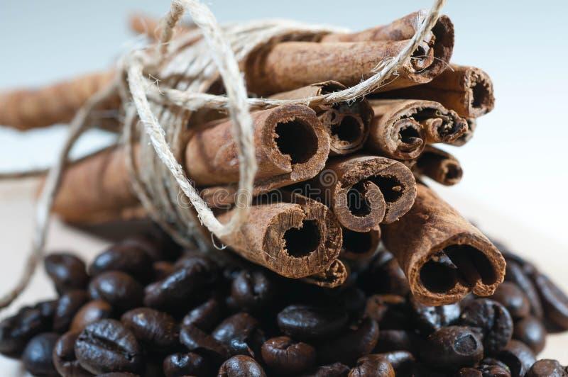 Bâtons de cannelle avec la corde sur les grains de café noirs photos stock