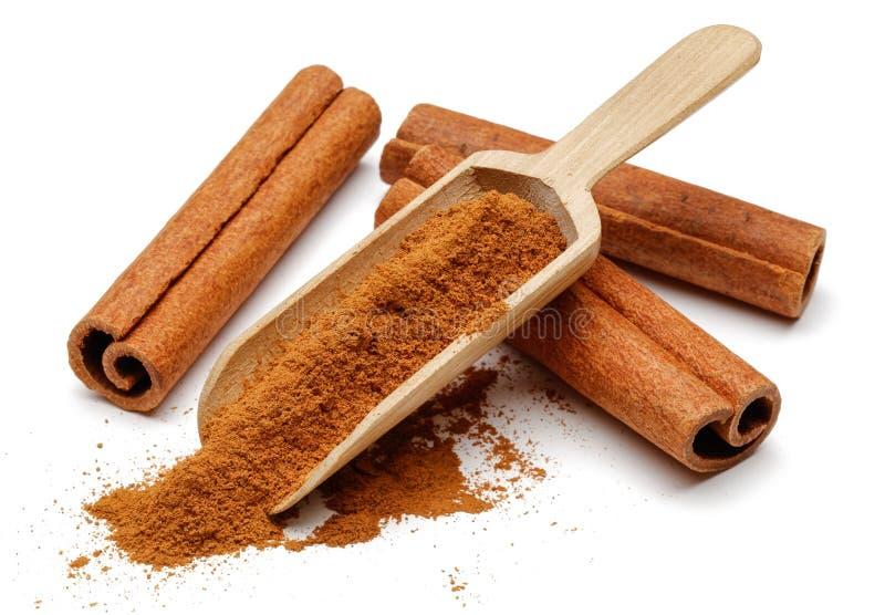 Bâtons de cannelle avec la poudre et le scoop en bois photo libre de droits