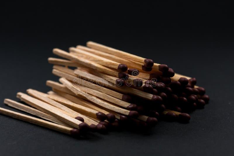 Bâtons de match accumulés sur l'un l'autre Bâtons de match et fond noir photo stock
