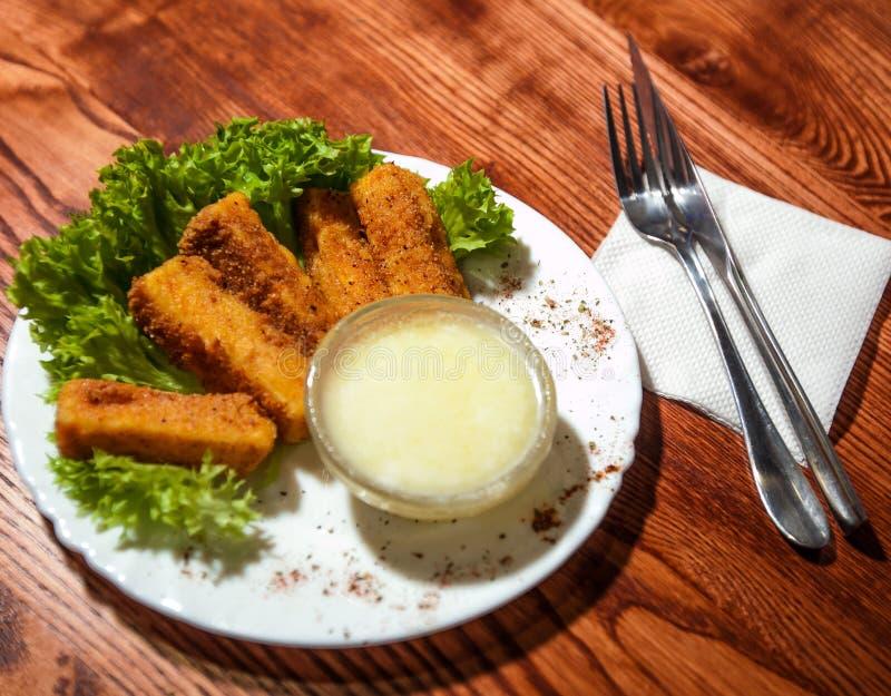 Bâtons de poissons avec de la salade d'un plat blanc photographie stock libre de droits