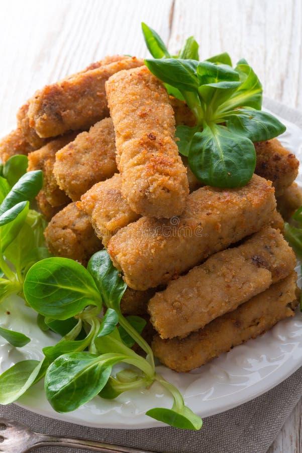 Bâtons de poissons faits à la maison avec de la salade images stock
