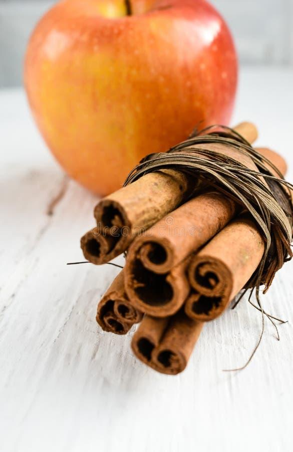 Bâtons et pomme de cannelle sur l'ingrédient en bois de table images libres de droits