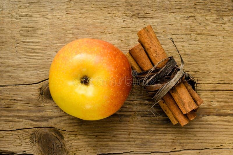 Bâtons et pomme de cannelle sur l'ingrédient en bois de table photographie stock libre de droits