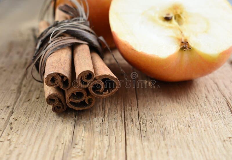 Bâtons et pomme de cannelle sur l'ingrédient en bois de table photos libres de droits