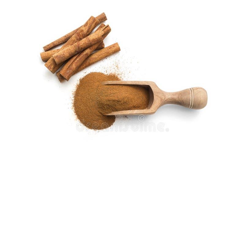 Bâtons et poudre de cannelle dans un scoop en bois image stock