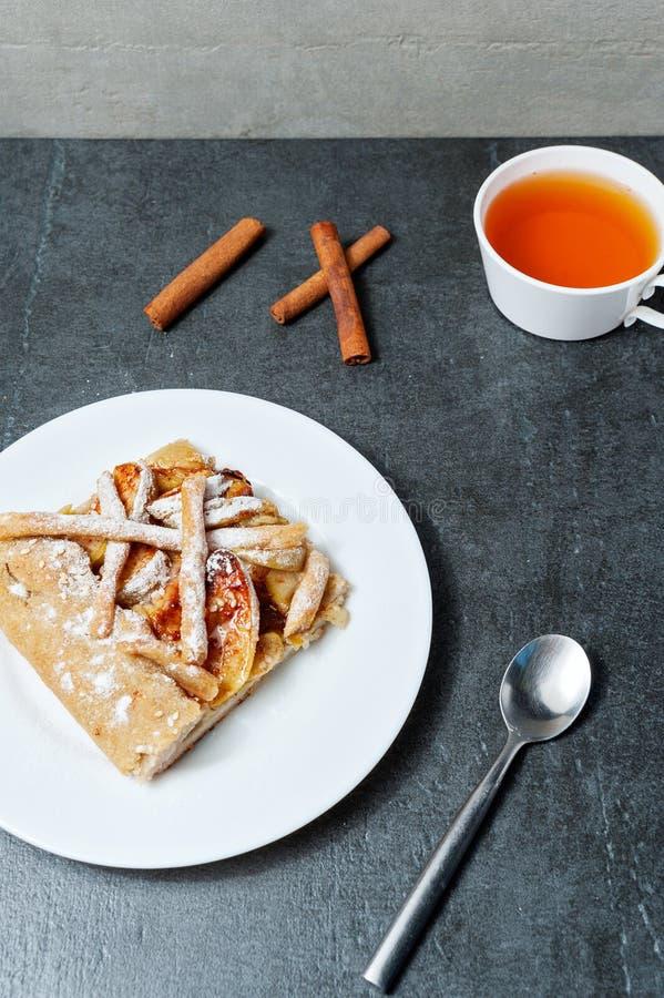 Bâtons faits maison de tarte aux pommes et de thé et de cinnamone sur le fond foncé image stock