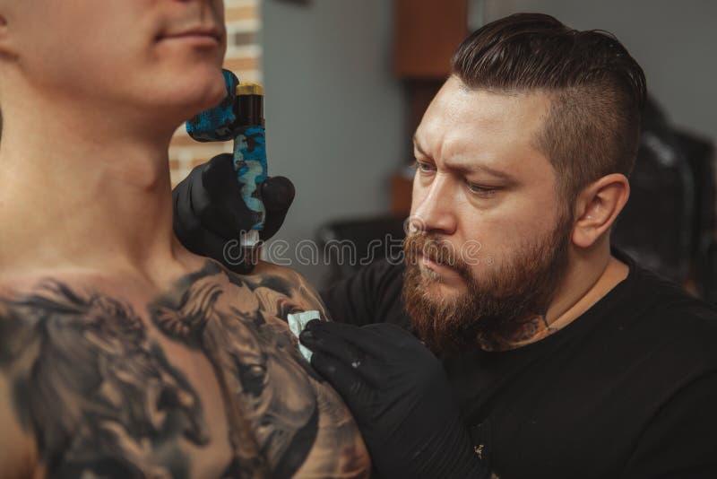 Bärtiger Tattooist, der Tätowierungen auf Körper seines Kunden macht lizenzfreie stockbilder