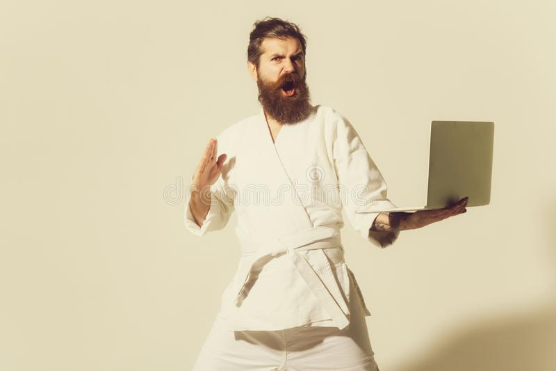 Bärtiger verärgerter Karatemann im Kimono mit Laptop stockfotos