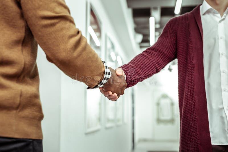 Büroangestellter in der weißen Hemd- und Burgunder-Wolljacke, die Hände rüttelt stockfoto