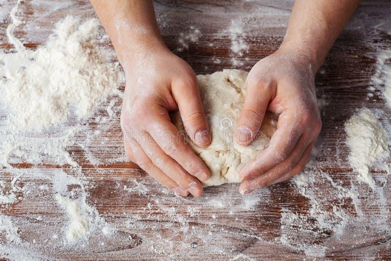 Bäcker bereitet den Teig auf einem Holztisch, männliche Hände kneten den Teig mit Mehl zu lizenzfreies stockfoto