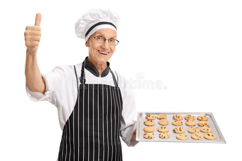 Bäcker, der Behälter mit Plätzchen hält und Daumen herauf Zeichen herstellt stockbilder