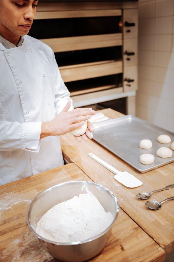 Bäcker, der etwas Mehl bei der Formung von kleinen runden Brötchen addiert stockfotografie