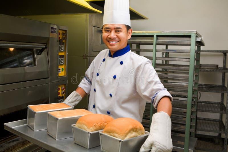 Bäcker, der frisches Brot vom Ofen anhält lizenzfreie stockbilder