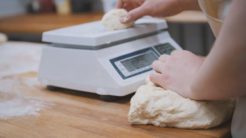 Bäcker, der Teig für das Backen wiegt stockbilder