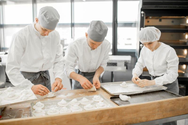 Bäcker, die Brötchen an der Herstellung machen lizenzfreie stockfotos