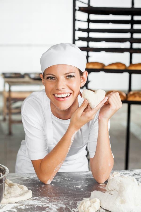 Bäcker-Holding Heart Shape-Teig beim an sich lehnen lizenzfreie stockfotos