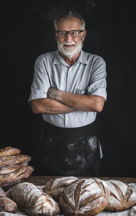 Bäcker mit einer Zusammenstellung des frischen Brotes lizenzfreie stockfotografie