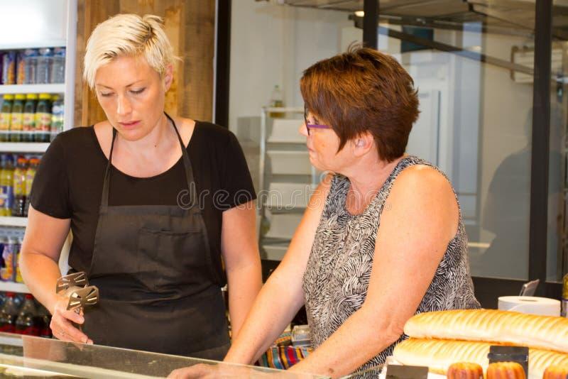 Bäcker mit zwei Frauen, Verkäuferin in der Bäckerei, die frische Bäckereiprodukte verkauft lizenzfreie stockbilder