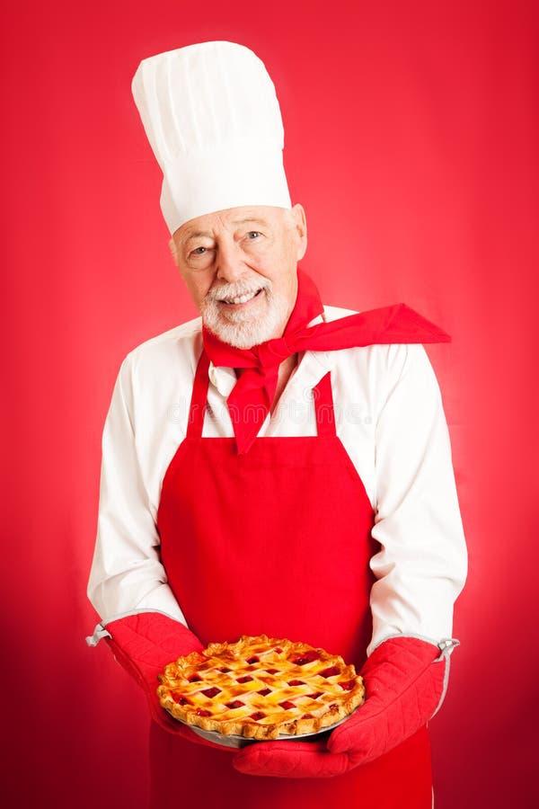 Bäcker, der Kirschtorte hält lizenzfreie stockfotos