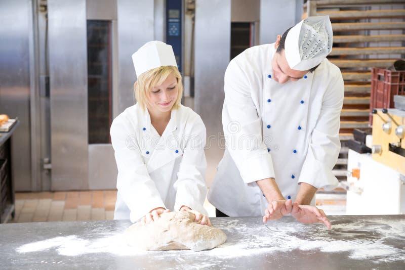 Bäckeranweisungslehrling in knetendem Brotteig lizenzfreies stockfoto