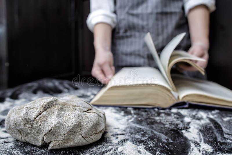 Bäckerchef, der nach einem Rezept in einem Kochbuch sucht stockfotografie