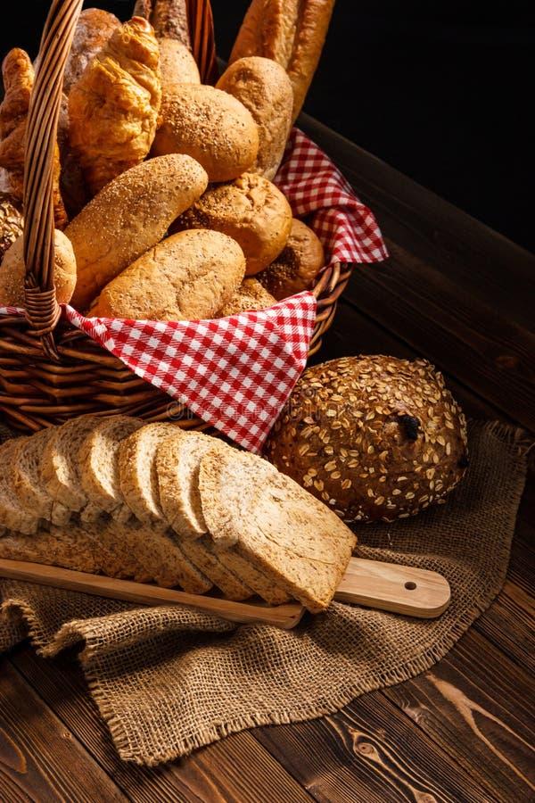 Bäckerei-Zusammenstellung auf Holztisch auf dunklem Hintergrund Stillleben von Vielzahl des Brotes mit natürlichem Morgenlicht stockfoto