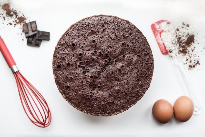 Bäckereibestandteile - Mehl, Eier, Kakao, Schokolade auf weißer Tabelle Süßes Gebäckbackenkonzept Flache Lage, Kopienraum, Draufs stockfoto