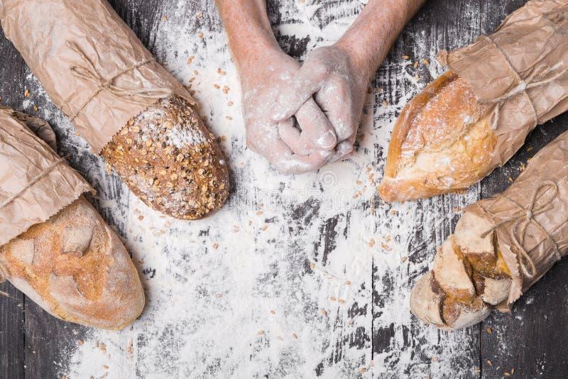 Bäckereikonzepthintergrund Hände und Art des Brotlaibs lizenzfreies stockbild