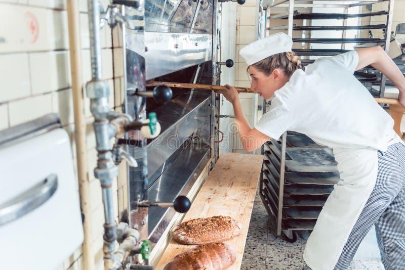Bäckerfrau, die Brot aus Backofen heraus erhält lizenzfreies stockfoto