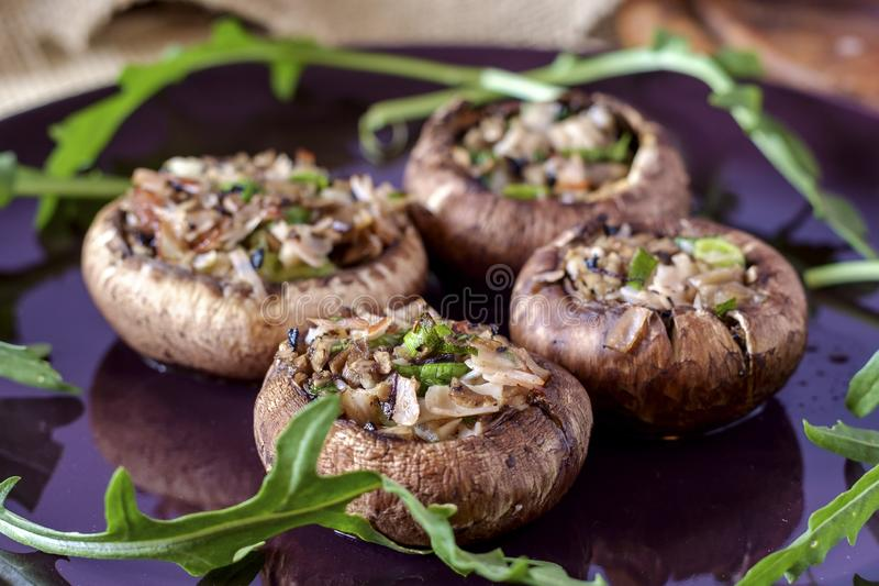 Bädda bruna svampar fyllda med skinka, vitlök, svamp, lök och persilja arkivbild