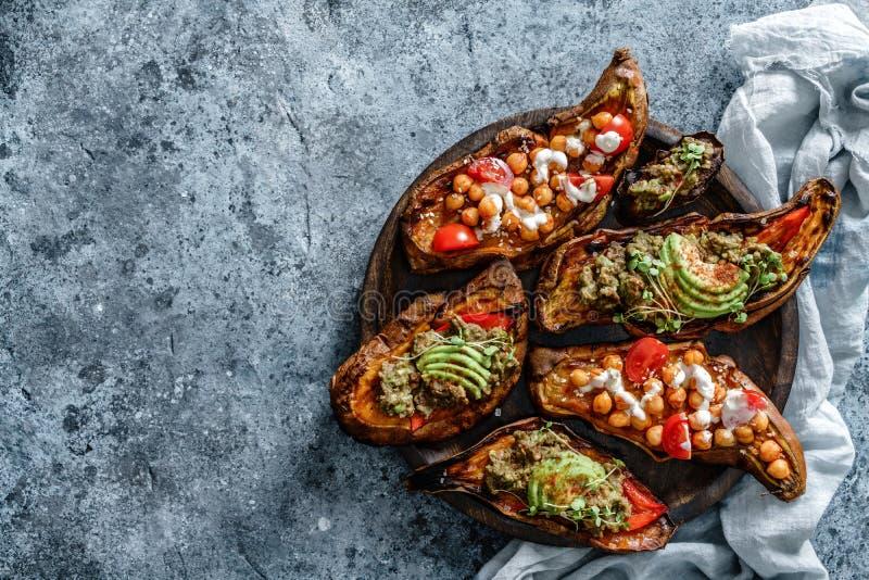 Bädda sötpotatiskål med rostade kikärter, tomater, getost, såsguacamol, avokado, sallat på träskivor över arkivfoton
