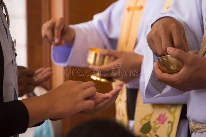 Bägaren och prästens hand royaltyfria foton