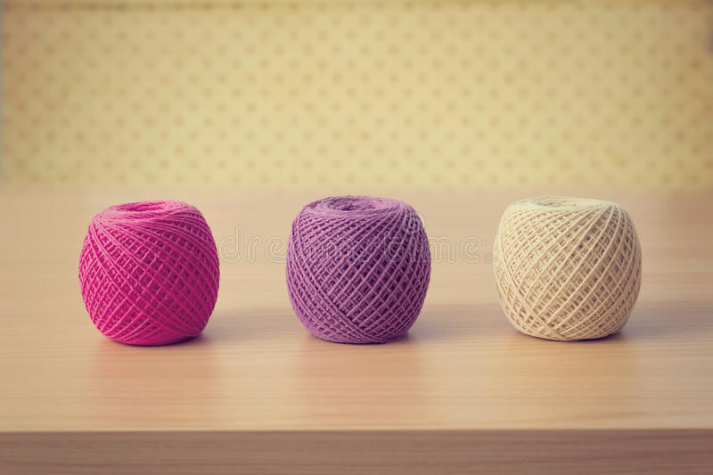 Bälle von Threads auf einem Holztisch über Weinlese tapezieren stockfotos