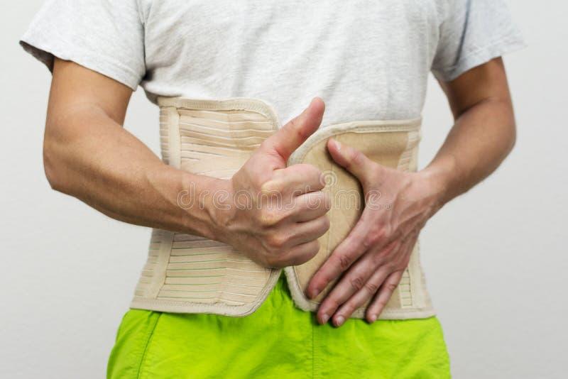 Bälte för mandressingryggstöd vid hans händer arkivbild
