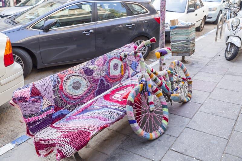 Bänk, cykel och pol som täckas med färgrika handarbeten royaltyfri foto