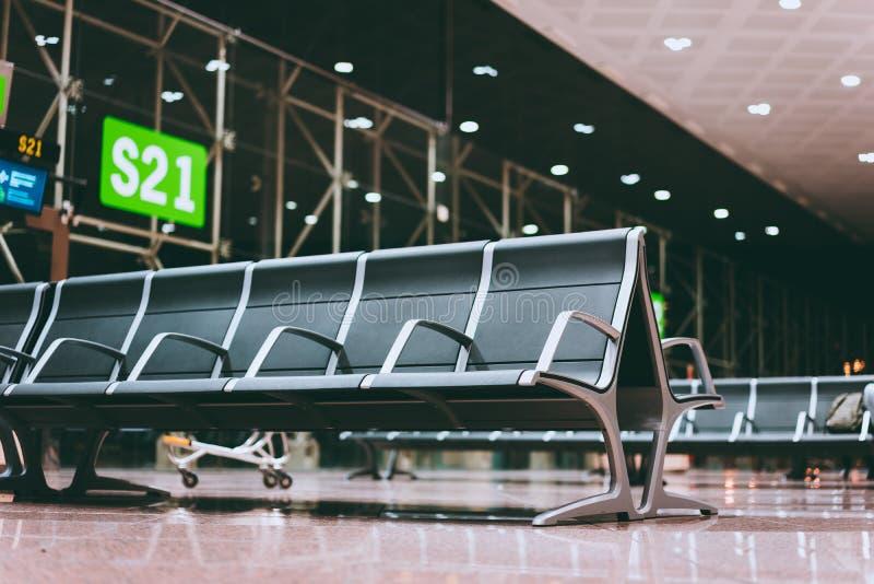 Bänk för tomma platser i flygplatskorridoren nära avvikelseporten på den internationella flygplatsen Väntande på logi på natten arkivbilder