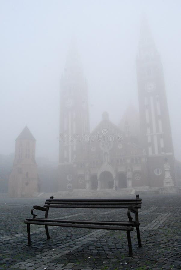 Bänk i en dimmig fyrkant med en kyrka royaltyfria foton