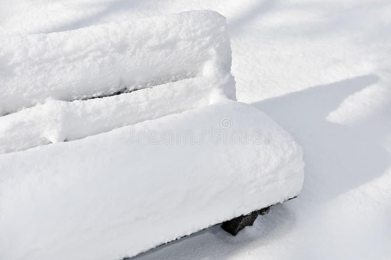 Bänk i en parkera som fullständigt täckas av snö arkivfoton