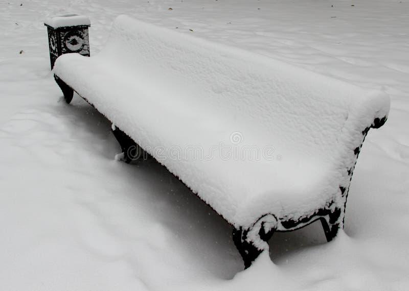 Bänk i en parkera som täckas fullständigt i snö efter tungt snöfall arkivfoton