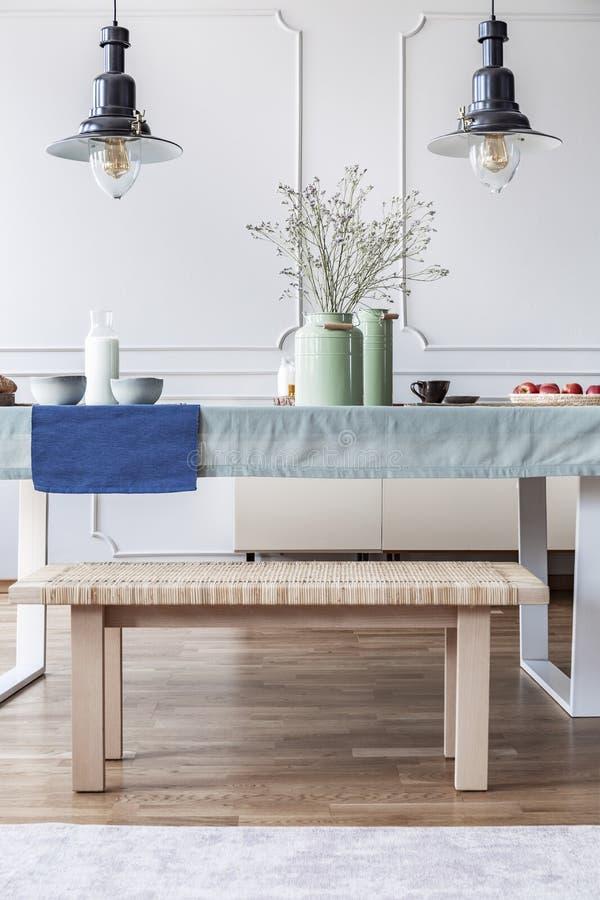 Bänk och blå torkduk på en tabell i en matsalinre Verkligt foto arkivbild
