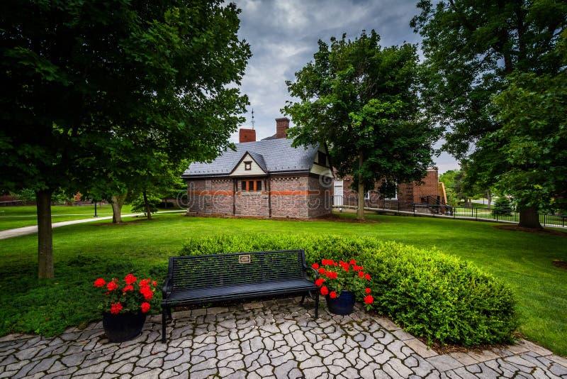 Bänk och byggnader på universitetsområdet av den Gettysburg högskolan, i Gett royaltyfri fotografi