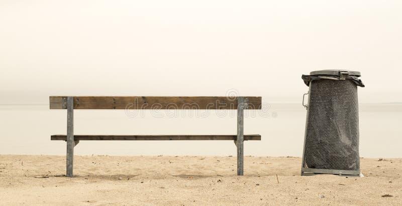Bänk och soptunna på stranden vid havet fotografering för bildbyråer