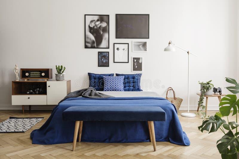 Bänk på en träfiskbensmönsterparkett i en ljus och konstnärlig sovruminre med marinblåa textiler royaltyfria foton