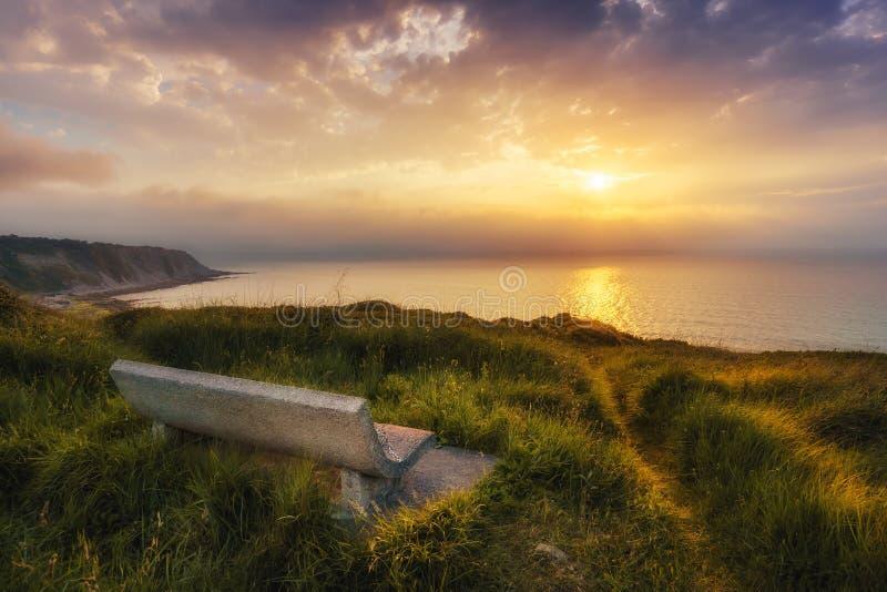 Bänk på solnedgången med sikt av den Azkorri stranden i Getxo royaltyfria foton
