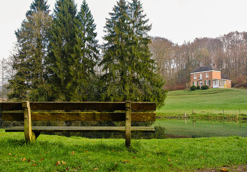 Bänk vid sjön och huset på kullarna royaltyfri foto