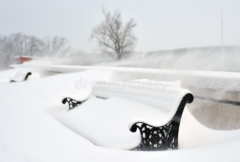 Bänkar i parkera som täckas med snö arkivfoto